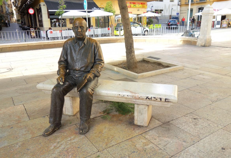 Da  sitzt der Künstler ganz allein auf einer Bank an der Plaza de la Merced