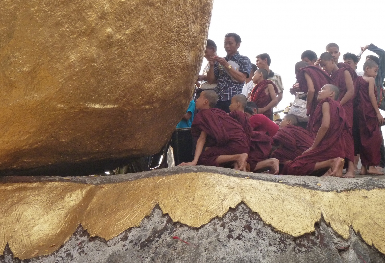 """Mönche in Myanmar bekleben den """"Golden Rock"""", einen mystischen Felsbrocken,  mit Goldplättchen."""