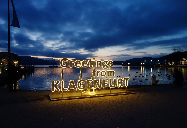 Grüße aus Klagenfurt blinkt es am Wörthersee.