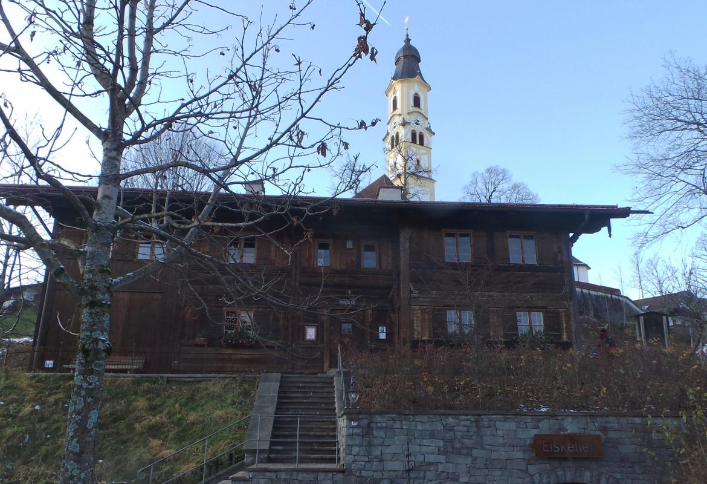 Der Kirchturm von Sankt Nikolaus überragt das schöne Heimathaus in Pfronten.